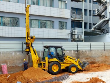 Bulldozer with bore pile rig at the construction site