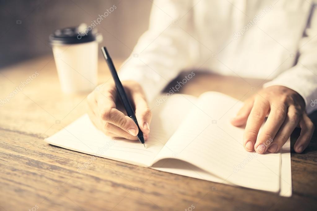 Fille écrit dans le bloc notes sur un bureau en bois avec une