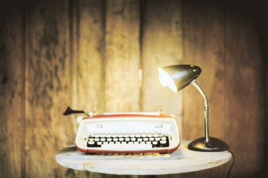 Typing machine and lamp on wood