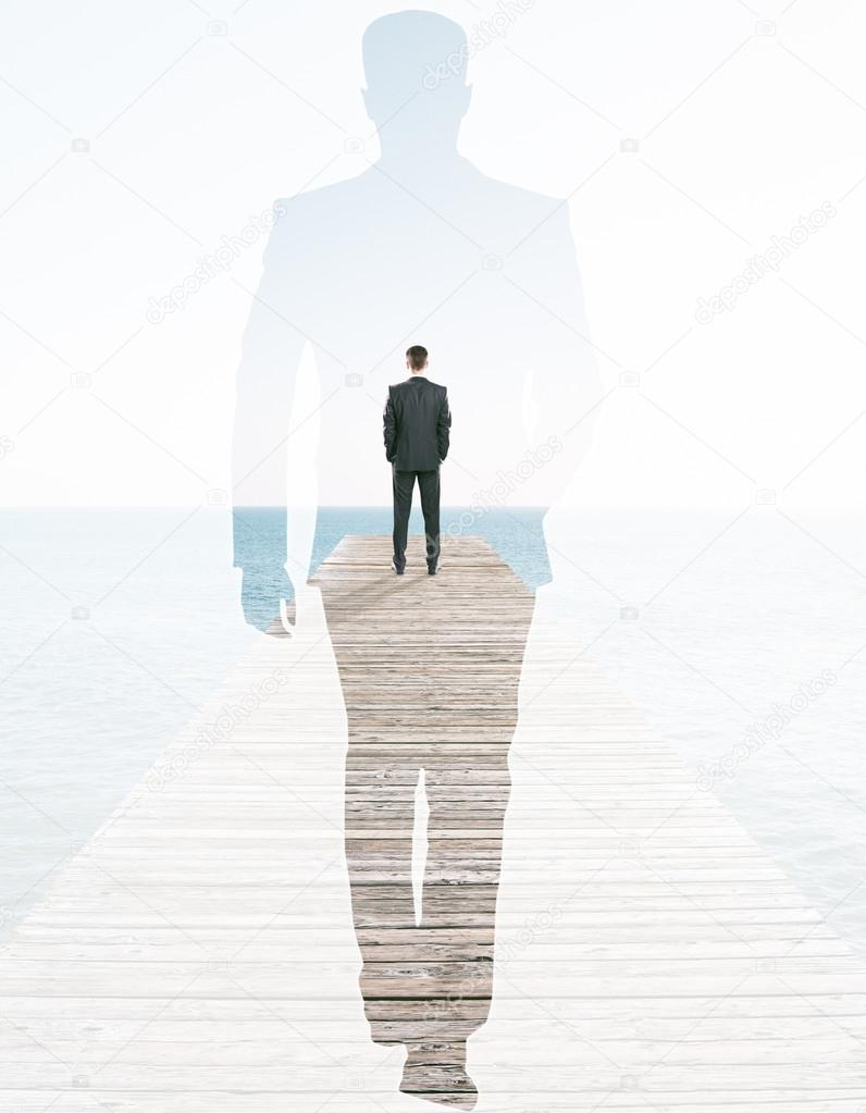 back view of businessman on pier and walking male silhouette on sea