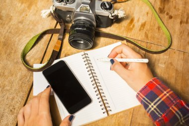 Girl writes in notebook with old camera