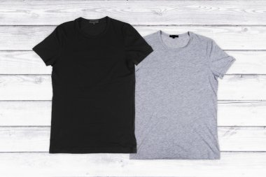 two blank t-shirts on a white wooden background