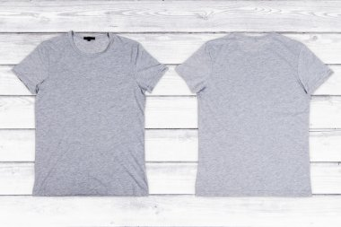 Two gray blank T-shirts on a white wooden background
