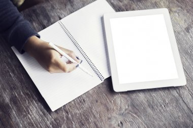 Girl writes in a notebook lying beside a blank digital tablet