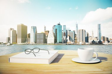 Book, cup of coffee and eyeglasses