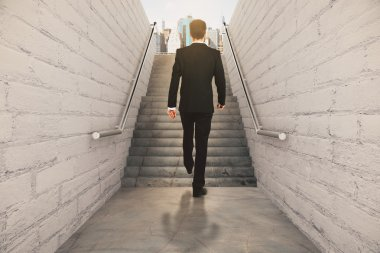 Businessman isclimbing up the stairs between brick walls and con