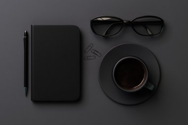 black diary cover, cup and glasses