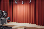 Fotografie Empty stage with red scenes, spotlights and vintage movie camera