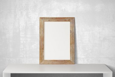 Blank wooden picture frame on white table and concrete floor, mo