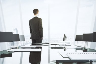 Businessman looks out the window in conference room with glassy