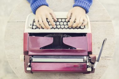 Top view on the girl with vintage typewriter on wooden table