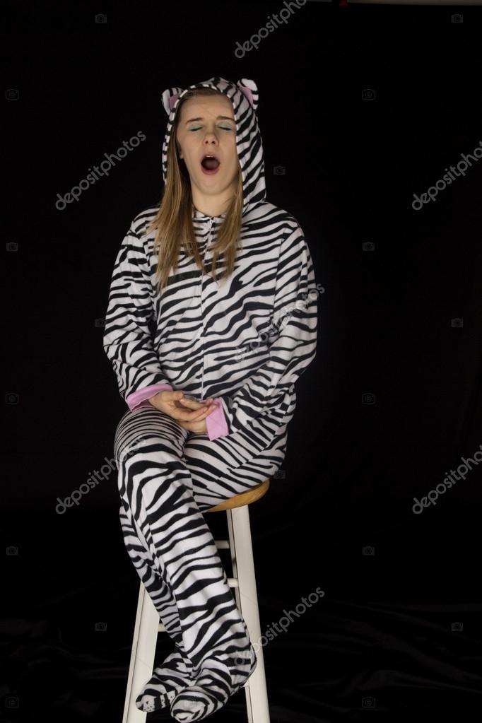 7b7544f32a Modelo de mujer joven vistiendo pijamas gato bostezando y sentado en la  calle — Foto de