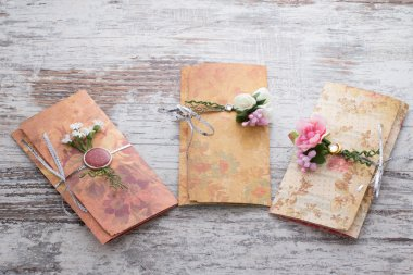 Handmade wedding invitations made of paper pver wooden vintage backgroundd