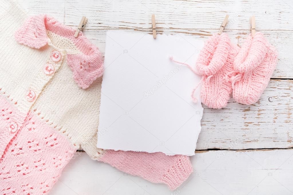 baby girl clothes with blank card on white wooden background flat