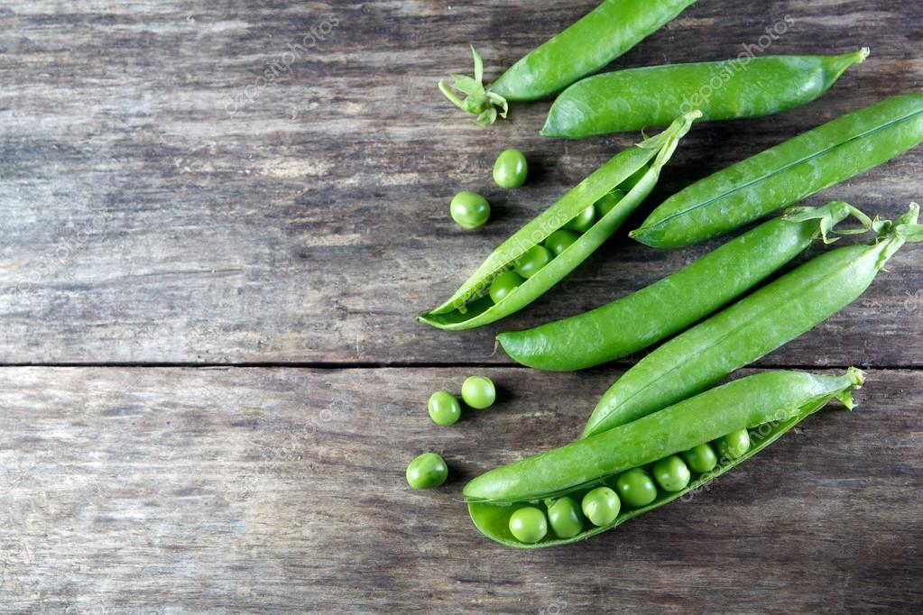 Pod of green peas on wood