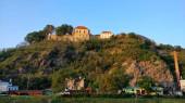 Burg Znojmo auf dem Hügel von der Flussseite aus gesehen. Himmel hat schöne saubere blaue Farbe. Der Felsen ist mit Büschen bedeckt. Es gibt auch einige Gebäude auf dem Grund des Felsens. Das Wetter ist warm und angenehm.