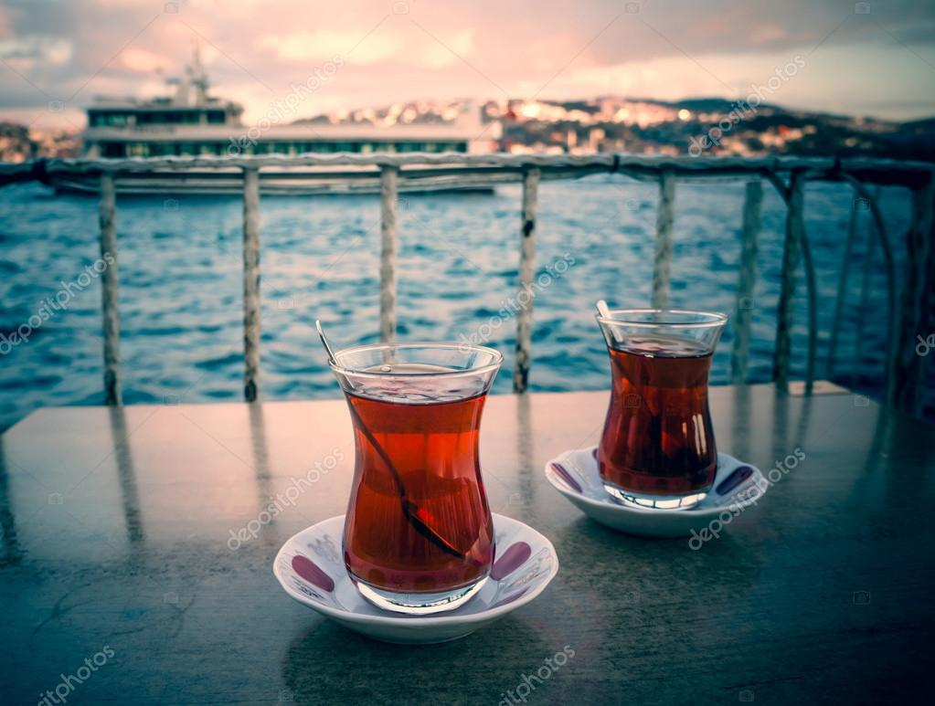 Two glasses of turkish tea on the table with Bosphorus on the background in Istanbul, Turkey. Toned image