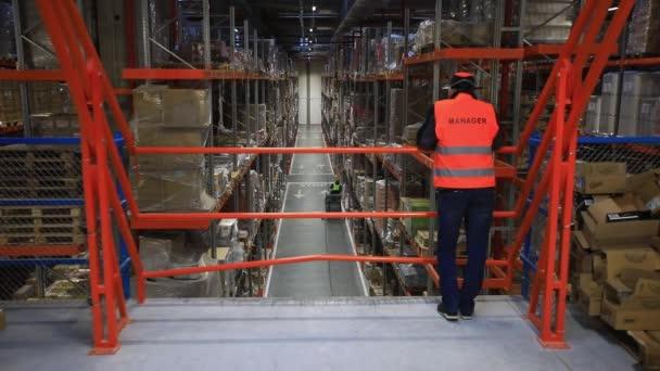 Raktár kartondobozokkal raklaptartókon, logisztikai központ.