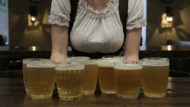 Waitress puts a full beer mugs on the table