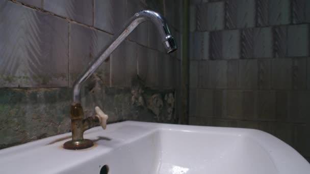 Zpomalení natáčení kapající vody z kohoutku ve špatné koupelně