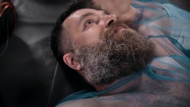 Tvář vousatého muže ležícího na podlaze s ostatními lidmi