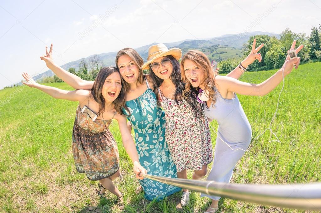 Multiracial girlfriends taking selfie with stick at country picnic - Happy friendship concept and fun with young people having fun together - Sunny afternoon warm color tones and tilted horizon