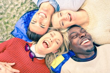 Multiracial best friends having fun and laughing together outdoor at springtime - Happy friendship concept with young people on fashion clothes - Upside down point of view - Soft vintage filtered look