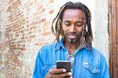 Africké americké mladý muž pomocí mobilní mobilní telefon - model Hipster chlap s moderní smartphone - mužský módní člověk s mobil a dredy účes - konceptu integrace a nové technologie