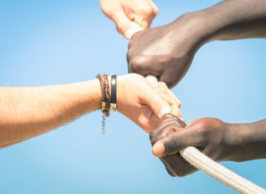 Tug of war - Concept of interracial multi ethnic union together against racism - Multiracial hands teamwork