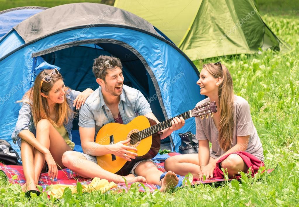 Group of best friends singing and having fun camping together - Concept of carefree youth and freedom outdoors in the nature - Caucasian young people during vacations