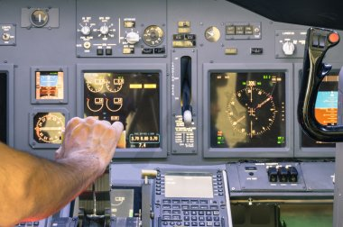 Captain hand accelerating on the throttle in commercial airliner flight simulator - Cockpit thrust levers on the phase of takeoff