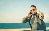 Fotografie Koncepce technologií spojených s životním stylem cestovatel - mužský model znázorňující úspěch pro mobilní telefonní společnost