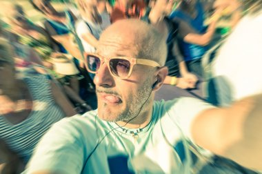 Bald funny man taking a selfie in the crowd with stupid tongue out expression - Travel lifestyle enjoying moment of carefree loneliness - Vintage filtered look