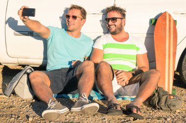 Young hipster best friends taking a selfie sitting next to the car - Concept of modern technologies mixed with vintage lifestyle - Adventurous friendship during travel and