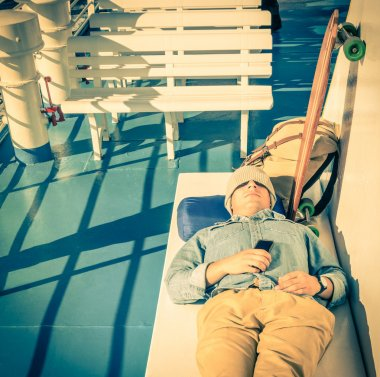 Young hipster man having a rest during a ferry boat passage holding his smartphone  - Modern concept of freedom and alternative lifestyle - Cheap travel backpacking around the world