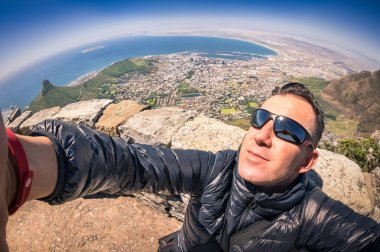 Modern handsome young man taking a selfie at Table Mountain in Cape Town - Adventure travel lifestyle enjoying connection with nature - Trip excursion in South Africa at nature wonder destination
