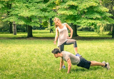 Girlfriend mocking her boyfriend while training in the park - Young man and woman during spring workout and sport activity - Male and female happy couple fitness models exercising after running