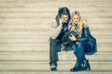 Beautiful hipster couple in love having a smartphone call - Modern concept of connection in a relationship together with mobile phone technology - City stairs urban lifestyle and everyday life rapport