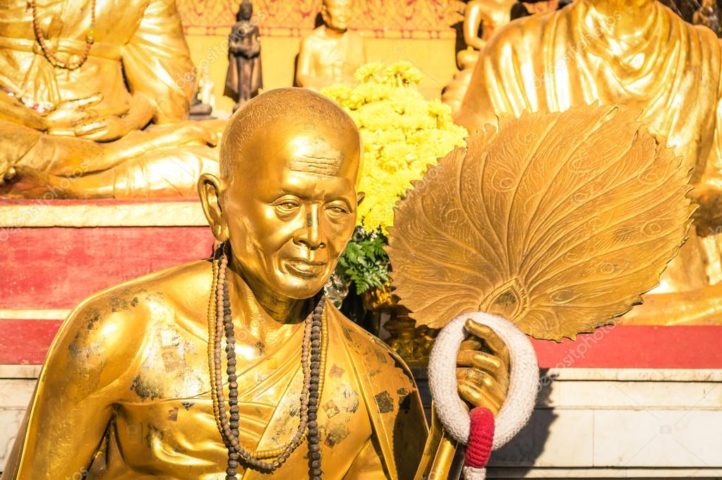 Golden statue of old buddhist monk with flowers ring in the sanctuary of Doi Suthep - Ancient buddha temple in Chiang Mai province in Thailand - Concept of faith and religion in asian countries