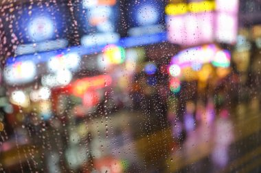 Emotional abstract background with defocused lights bokeh at NathanRoad in Hong Kong behind rain drops in window glass - Focus on few drops due to the shallow depth of field