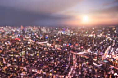 Aerial bokeh of Tokyo skyline from above during sunset and blue hour - Japanese world famous capital with spectacular nightscape panorama - Violet marsala filter on blurred defocused night lights
