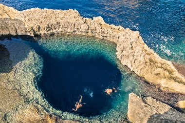 Deep blue hole at the world famous Azure Window in Gozo island - Mediterranean nature wonder in the beautiful Malta - Unrecognizable touristic scuba divers swimming to adventure water cave