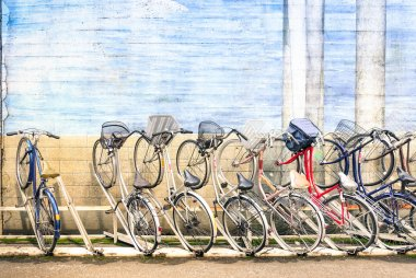 Multicolored vintage bicycles in metal rack in Tokyo city - Urban ecological transportation concept with retro bikes - Ryogoku residential district in the japanese world famous capital - Logos removed