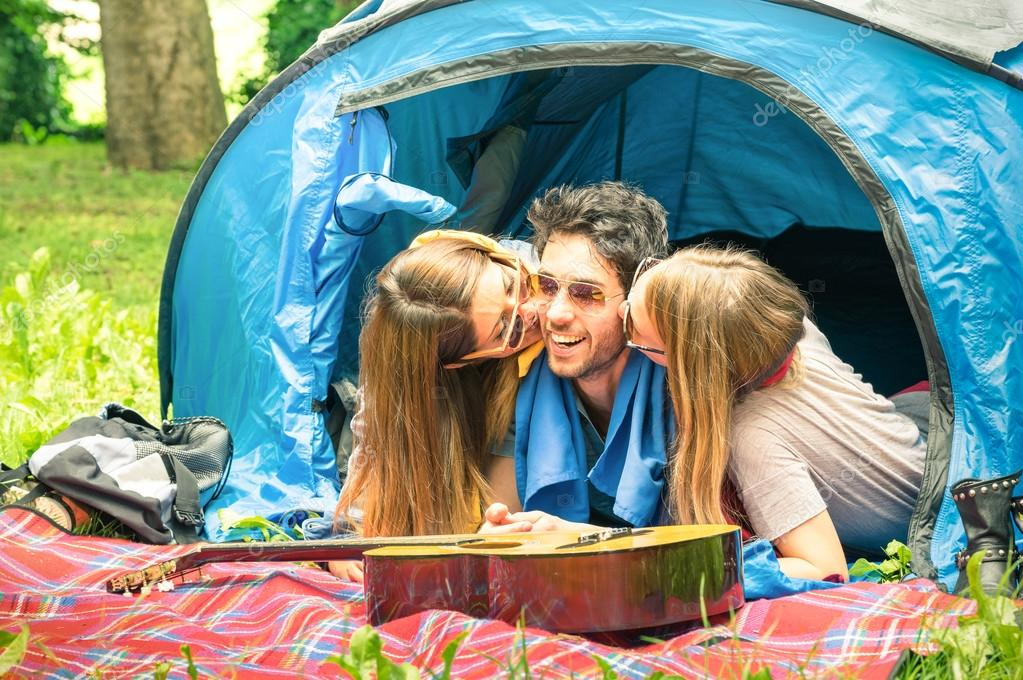 Group of best friends having fun camping together - Concept of carefree youth and freedom outdoors in the nature - Young people during vacations with lucky man flirting with beautiful girlfriends