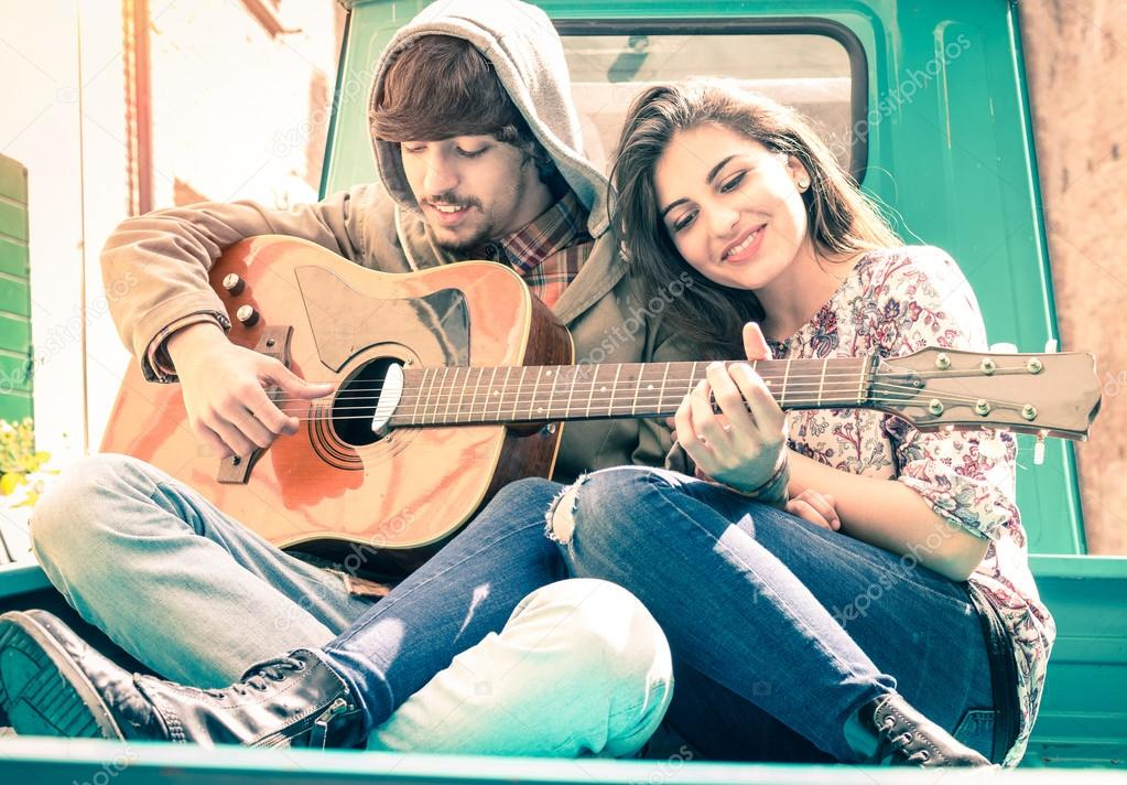 Romantic couple of lovers playing guitar on old fashioned mini car - Nostalgic retro concept of love with soft focus on the faces of boyfriend and girlfriend - Overexposed desaturated vintage filter