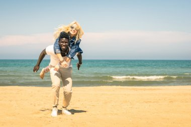 Young multiracial couple at the beach having fun with piggyback jump - Happy mixed race boyfriend and girlfriend playing at the beginning of love story - Multi ethnic integration love against racism