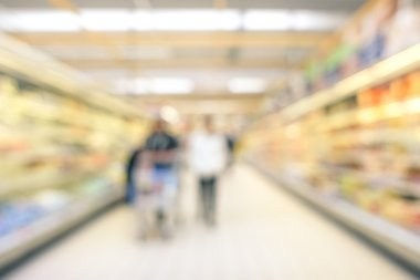 Blurred defocused background of generic supermarket lane- Concept of consumerism during a period of economic crisis - Neutral blur of couple of people in empty corridor at grocery commercial center