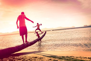 Father playing with sons at tropical beach with tilted horizon - Concept of  family union with man and children having fun together - Modified unrecognizable silhouettes - Marsala filtered color tones