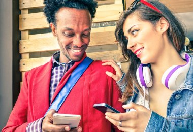 Multiracial couple flirting with smartphone numbers - Modern concept of mobile phone technology with happy people having fun - City urban lifestyle on natural light and warm vintage filtered editing