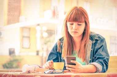 Vintage filtered portrait of serious pensive young woman with smartphone - Hipster girl using mobile smart phone while drinking coffee - Concept of human emotions - Soft focus on sad worried face